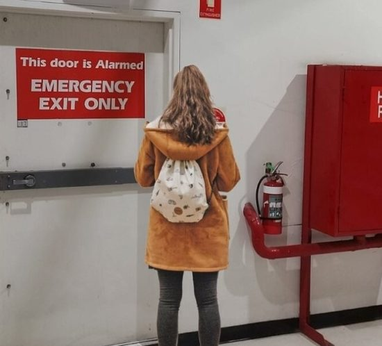 Girl standing in front of an emergency exit trying to decide whether or not to evacuate during an emergency.