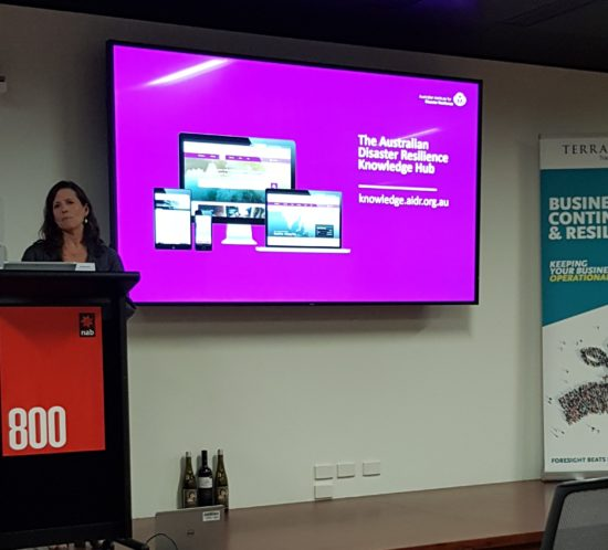 Image showing Amanda Lamont from the Australian Institute for Disaster Resilience standing at a lecturn with a screen to her left presenting a session on Supporting disaster resilience through knowledge sharing and connecting at the Business Continuity Awareness Week Forum 2018 in Melbourne